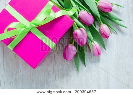Pink Tulip Flowers and Pink Giftbox on rustic table for March 8 International Womens Day Birthday Valentines Day or Mothers day - Top View