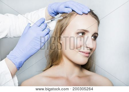 Doctor aesthetician with blue medical gloves and white medical gown makes hyaluronic acid rejuvenation beauty injections in the head of female patient for hair growth and to prevent boldness.