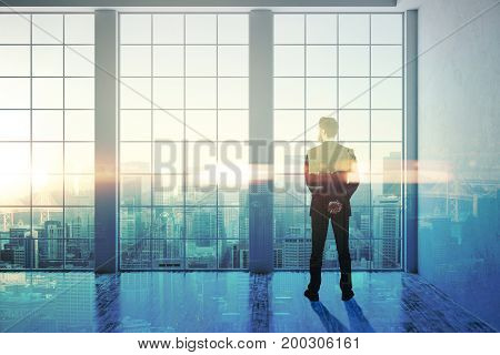 Back view of thoughtful young businessman in creative business interior looking at city with sunlight. Future concept. Double exposure