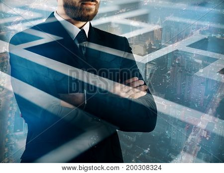 Thoughtful young businessman on abstract city background with maze labyrinth. Intelligence concept. Double exposure