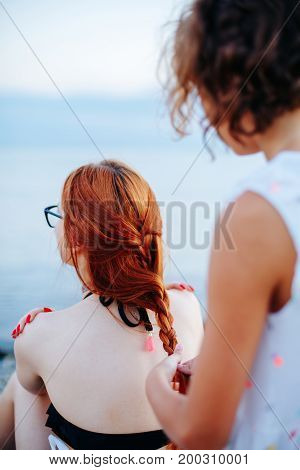 Anonymous woman standing behind redhead girl and braiding her hair on beach in sunlight.