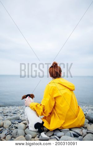 Back view of girl in yellow raincoat sitting with dog on pebble beach looking away at sea.
