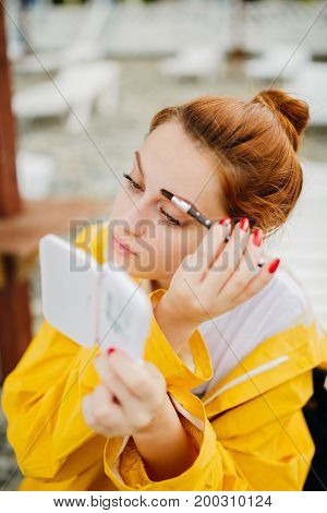 Young redhead girl doing eyebrows makeup looking at mirror