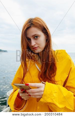 Portrait of young girl with red hair wearing bright coat and posing on ocean looking at camera.