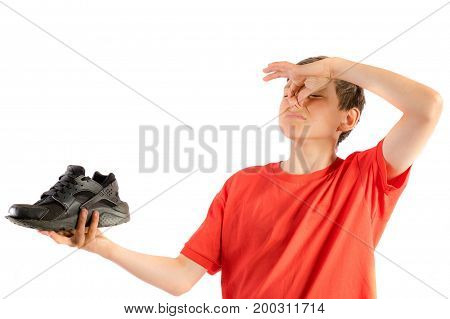 Young teenage boy isolated on a white background holding a smelly trainer