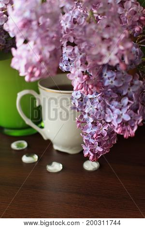 Porcelain teacup lilac bouquet and white decors on brown table
