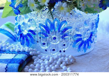 Composition with glass bowl linen napkin beaded necklace and artificial flowers on window sill