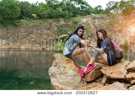 Young girl asian with backpack help friend hurt arm first aid elementary on the mountain travel trip adventure