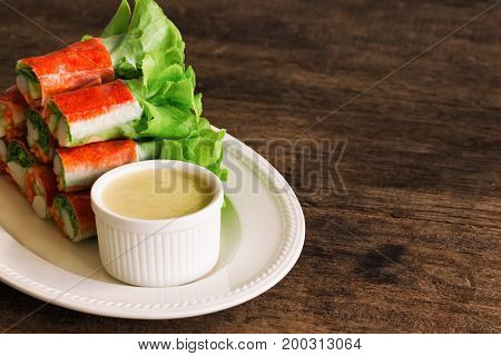 Fresh spring rolls with fresh vegetable and crab stick served with spicy salad cream dipping sauce.Rolls salad or fresh spring roll on white plate healthy delicious food for appetizer or meal. Homemade vegetable spring rolls or rolls salad.