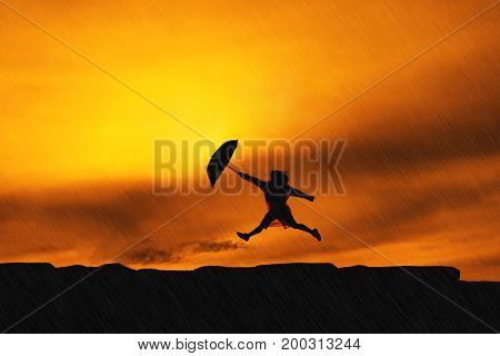 Young girl asian jumping with raincoat and umbrella on mountain in the rainy season silhouette