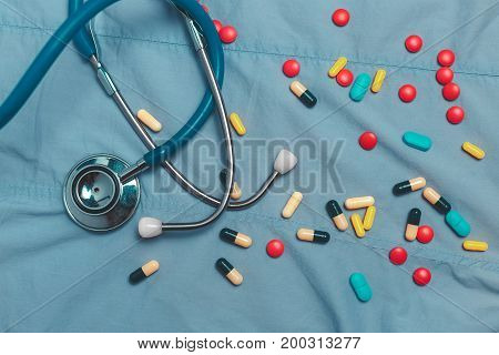 Assorted Colorful Pharmaceutical Medicine Pills Tablets And Capsules Over Blue Background