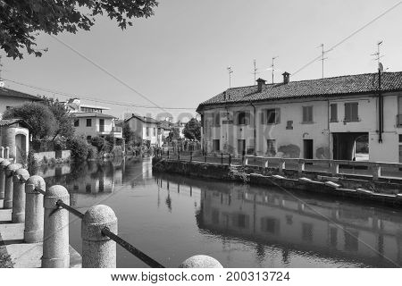 Gorgonzola (Milan Lombardy Italy): the canal of Martesana with historic buildings reflected in the water. Black and white