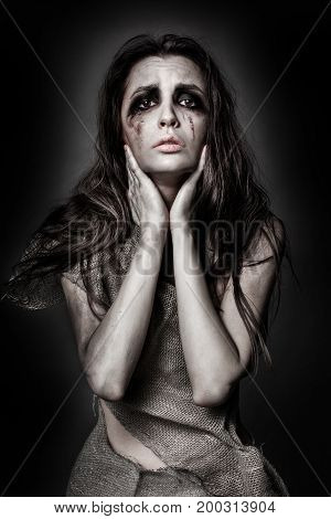 Sad woman on a dark background. Fear and despair. Emotional concept. Girl with smeared makeup.