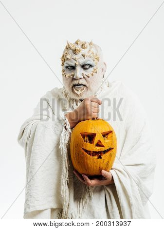 Wizard with blind eyes on white background. Demon with silver beard and hair. Monster with thorns on face. Halloween and horror concept. Man with orange pumpkin.