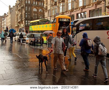 The wet street of Edinburgh. Edinburgh, Scotland - July 27, 2017 Movement of vehicles and people on the wet after a rain of street in Edinburgh.