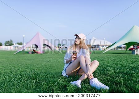 Young beautiful girl resting while sitting in an amusement park on green grass on a hot day with lemonade in her arms