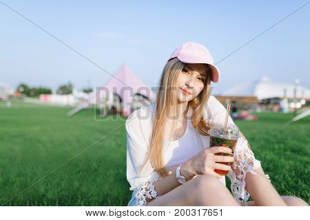 A stylish young woman with a cap resting in a beautiful modern park and holding a lemonade in her hands. Summer concept of rest.