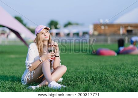 A stylish girl in a pink cap resting on a green lawn in the middle of a recreation park and holds a refreshing drink in her hands. Summer concept.