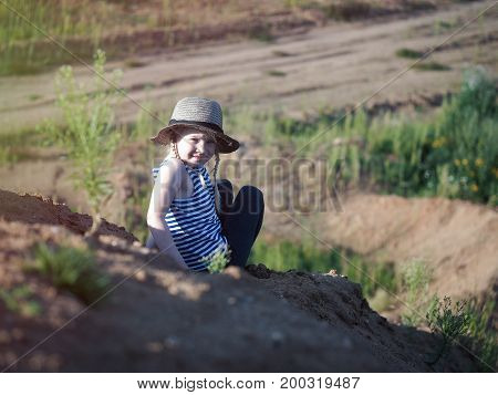 The child is sitting on a mountain of sand. A little girl wearing a hat and barefoot. Journey with the concept of children