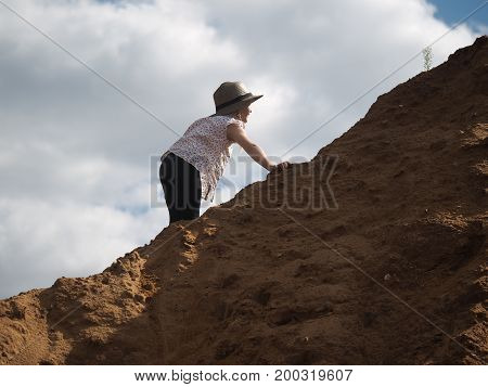 Child is climbing a mountain of sand. A little girl wearing a hat and barefoot. Journey with the concept of children