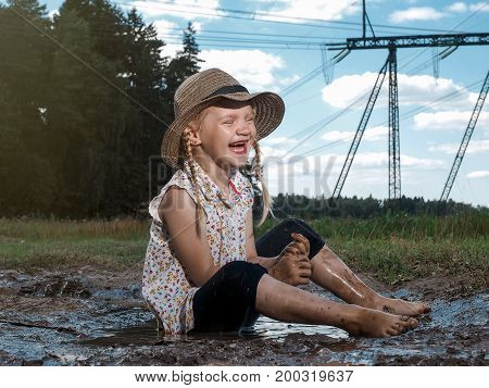 Extremely dirty baby laughing sitting in a puddle
