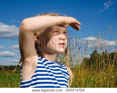 Portrait of a child on the background field and blue sky. The concept is to relax the children on nature travel. The girl looks into the distance