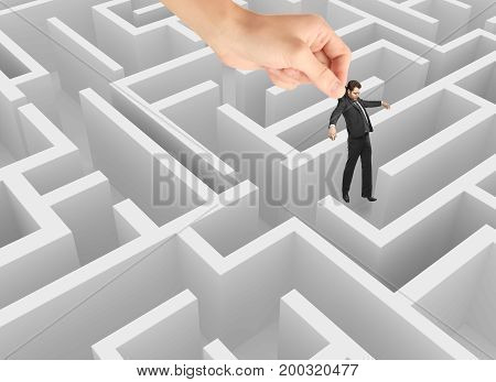 Hand placing businessman in abstract white maze. Complexity concept. 3D Rendering