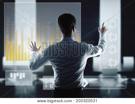Back view of young businessman using digital business screen. Technology and interface concept. 3D Rendering