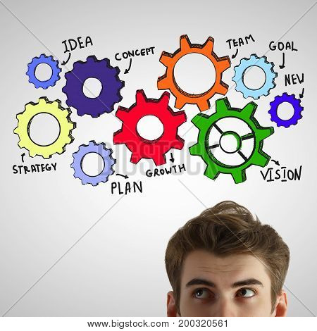 Portrait of attractive young man on light gray background with colorful cogwheels. Teamwork concept