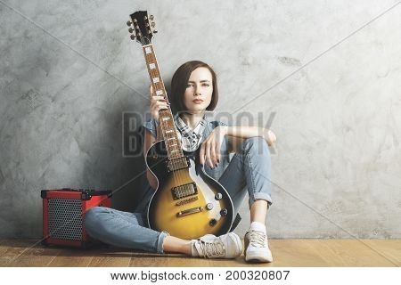 Pretty woman with electric sunburst guitar and amplifier sitting in studio room with wooden floor and concrete wall. Musician concert hobby leisure rehearsal concept