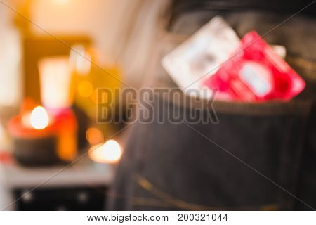 Blurred image style. Condoms in package in jeans with party background. Protection against AIDS. Safe sex concept. Protection against unwanted pregnancy.