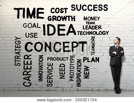 Handsome businessman with folded arms standing in brick interior with business words on wall. Leadership concept
