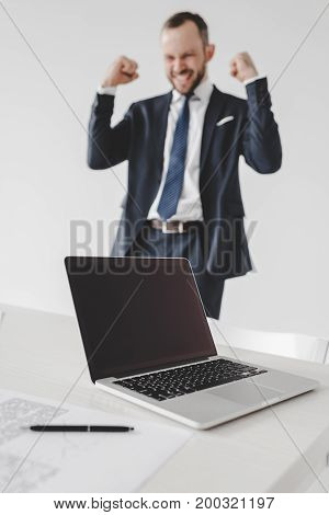 selective focus of laptop with blank screen and excited businessman behind