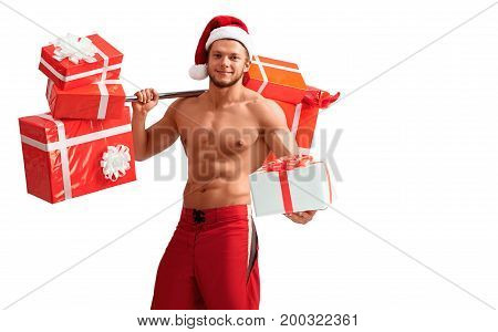 Christmas fever. Young fit guy with hot body holding out one of his presents isolated on white background with a copyplace on the side