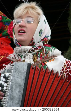 LUTSK UKRAINE - 10 January 2009: Woman with glasses and kerchief plays the accordion on the street