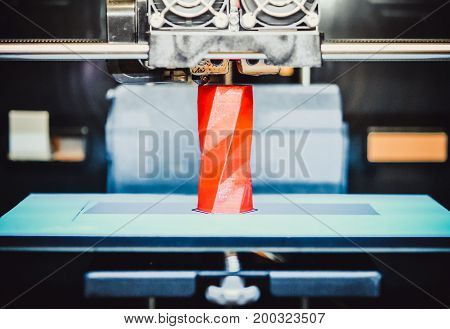 3D printer works and creates an object from the hot molten plastic close-up. Automatic three dimensional 3d printer performs plastic red colors modeling in laboratory.