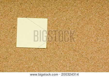 Blank sticky note on a cork bulletin board