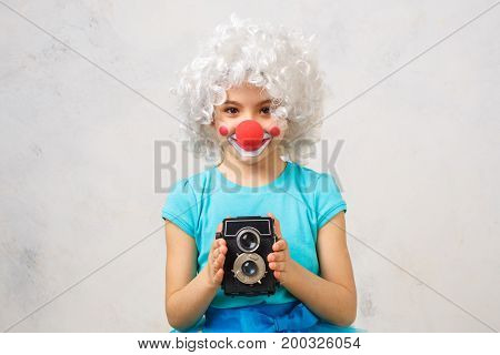 Little child wearing clown costume birthday celebration holding camera