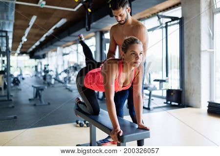 Young beautiful woman working exercises with trainer in gym