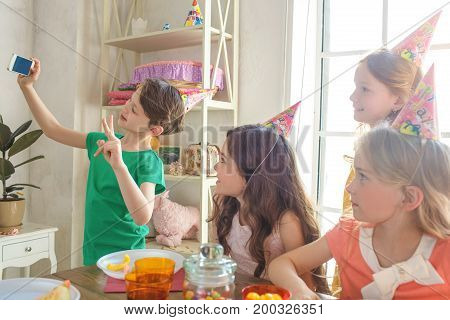 Little kids celebrating birthday together sitting at the table taking photos