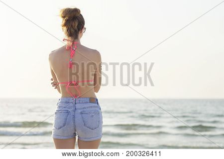 Young female in colorful bikini and denim shorts standing at the beach and looking at horizon. Lonely traveler at the seaside. Relax and enjoyment