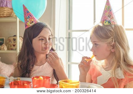Little kids celebrating birthday together sitting at the table eating