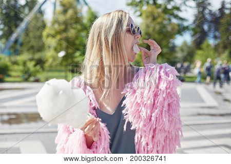 Young pretty fashionable teenage blond female is having fun in amusement park enjoying her vacation & sweet candy cotton putting peace on her mouth. European lady resting outside in pink funky coat.