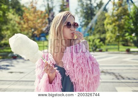 Young pretty fashionable teenage blond female is having fun in amusement park enjoying her vacation & sweet candy cotton. Caucasian woman resting outside in city park wearing pink extravagant jacket.
