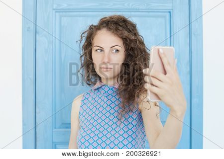Close up studio shot of young beautiful Caucasian curly haired female holding a smartphone digital camera with her hand and taking a selfie self portrait of herself standing against blue background.