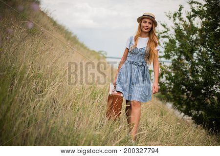 Girl With Suitcase On Grassland