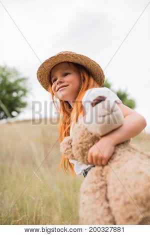 Child With Teddy Bear On Grassland