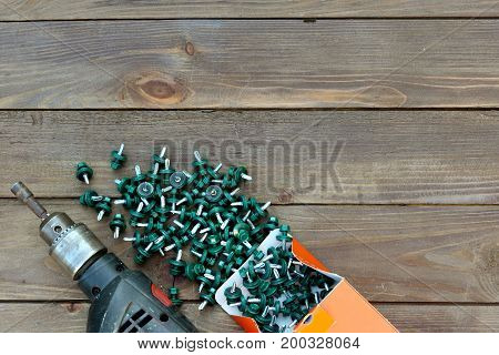 Roofing Screws And A Drill On A Wooden Table. The View From The Top. Template For Labor Day .roofer,