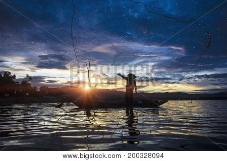 Silhouette Fisherman Fishing by using Net on the boat with sunlight in Thailand Nature and Culture concept