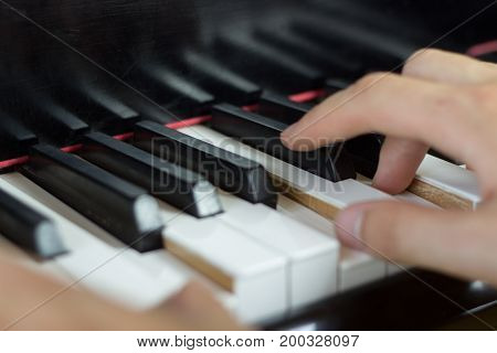 Close up of young hands playing piano